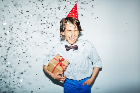 ecstatic: Ecstatic boy with packed birthday gift standing in confetti fall