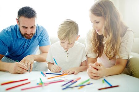 family together: Young parents and their little son drawing at home