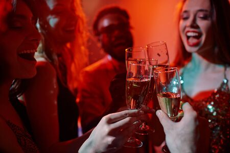 flutes: Friendly guys and girls clinking with flutes of champagne