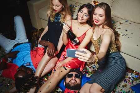 restful: Restful girls making selfie after party with two relaxing guys near by