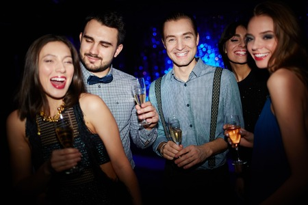 dancing club: Group of ecstatic friends with champagne dancing in night club Stock Photo