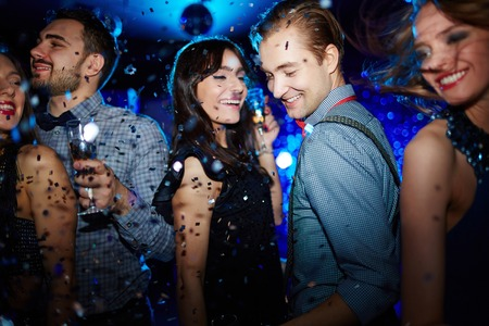clubber: Happy couple and their friends dancing under confetti rain at disco