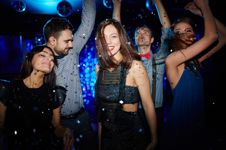 dancing club: Energetic young people dancing in night club under confetti Stock Photo