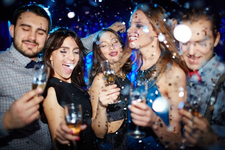 clubber: Group of ecstatic friends cheering with champagne at party in night club Stock Photo
