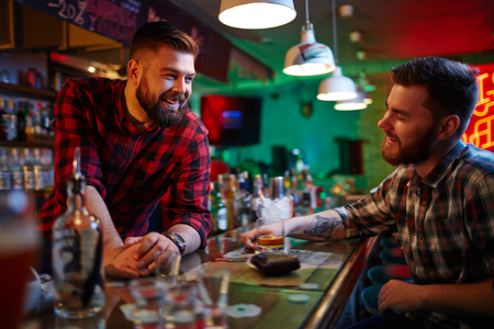barman: Happy barman and his friend talking in pub after-hours