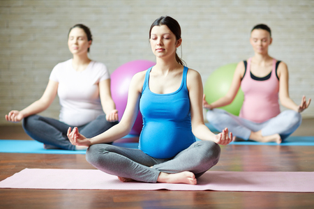 Group of young pregnant women practicing yoga
