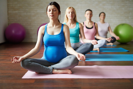 Grupo de futuras madres que practican ejercicios de yoga