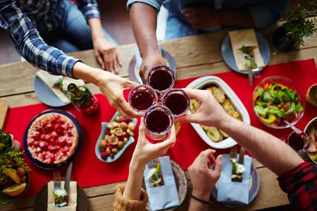 Groep vrienden roosteren met glazen rode wijn per feestelijke tafel
