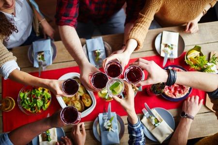 Grupo de amigos brindando con vino tinto durante la cena