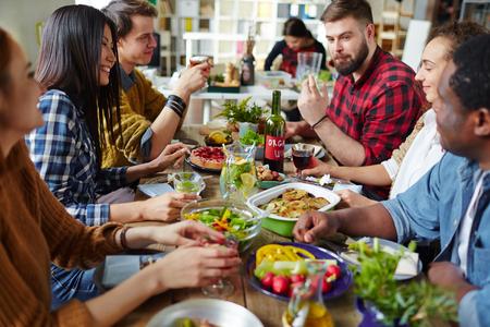 Gruppo di amici felici seduta da tavolo e una cena
