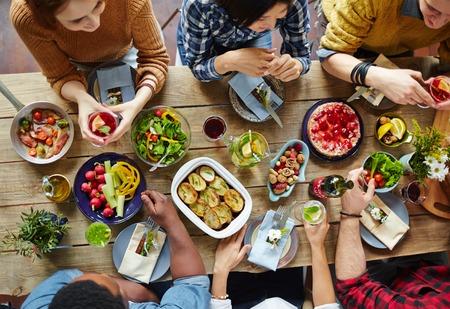 Intercultural friends eating tasty food by dinner