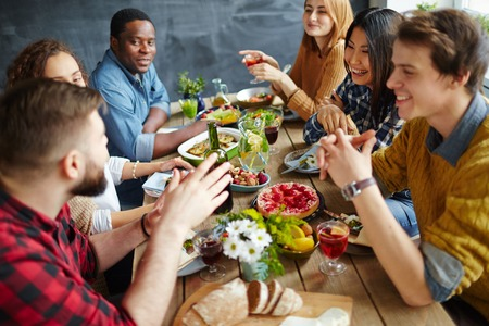 Group of happy friends having conversation by festive dinner Stock Photo