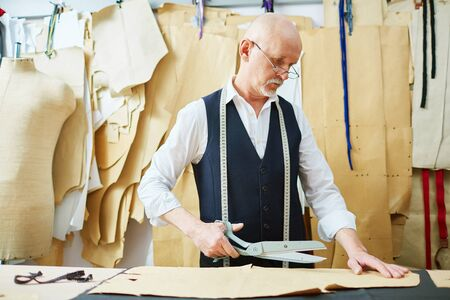 selfemployed: Mature tailor with scissors working with paper patterns