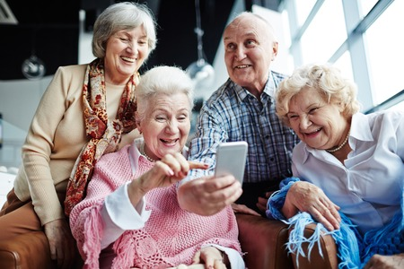 Group of friendly seniors with smartphone having fun in cafe