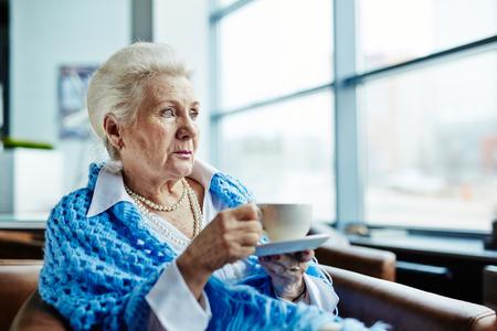Nachdenkliche ältere Frau mit Tee