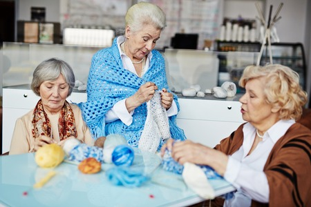 knitting: Group of elderly women knitting and talking by table