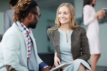 happy work: Happy businesswoman looking at colleague explaining his idea at meeting Stock Photo