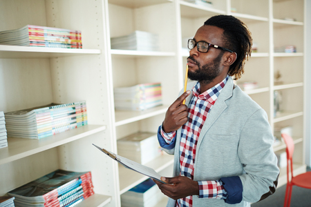 textbooks: Pensive office worker with clipboard looking at textbooks on shelves Stock Photo