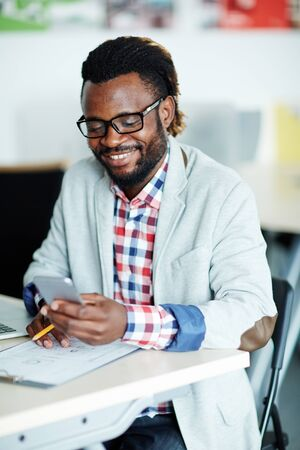 work addicted: Happy African-american businessman with smartphone reading sms