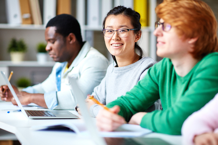 casual woman: Happy student looking at camera at lesson among her group-mates