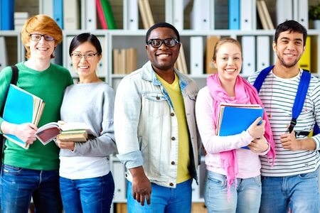 students group: Row of friendly students looking at camera in library Stock Photo