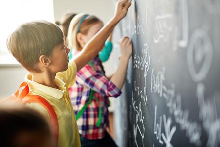 Clever schoolchildren doing sums on blackboard