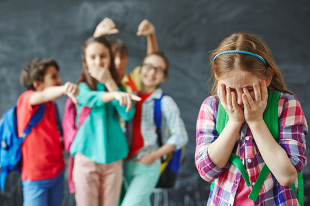 Unhappy schoolgirl hiding her face on background of teasing classmates