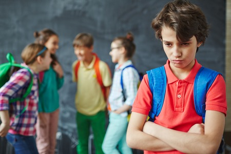 pupils: Offended schoolboy on background of chatting pupils