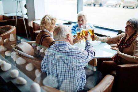 restful: Group of restful seniors having beer in cafe