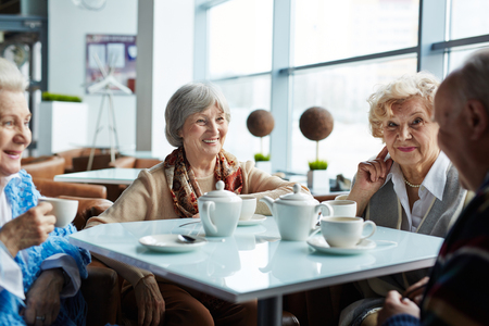 elderly people: Group of happy seniors having tea and rest in cafe Stock Photo