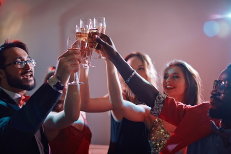 clinking: Happy young friends with flutes of champagne cheering up at booze