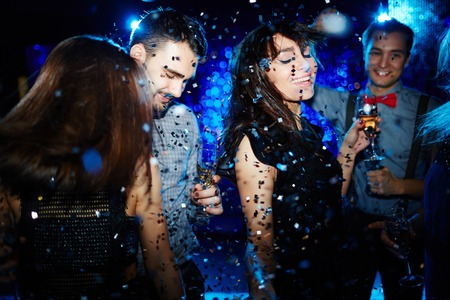 adult entertainment: Glamorous friends dancing in confetti