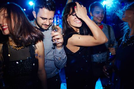dancing club: Group of happy friends dancing in night club