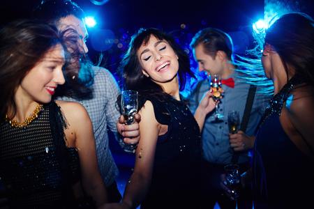 dancing club: Ecstatic young woman dancing in night club among her friends Stock Photo