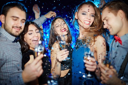 adult entertainment: Posh girls and guys with champagne cheering up in night club