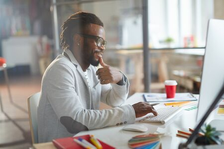 happy african: African designer working in front of computer monitor in office