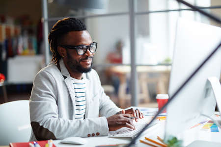 happy african: Young African businessman typing in office