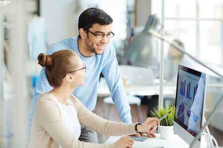 monitor de computadora: Empresaria en los datos financieros en el monitor del ordenador al explicar a su colega
