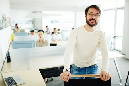 openspace: Happy Asian businessman looking at camera on background of working employees in open-space office