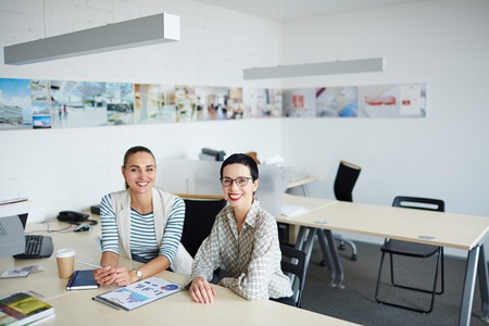 openspace: Happy colleagues sitting at workplace in open-space office Stock Photo