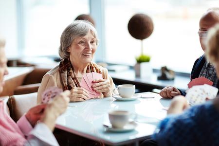 persona de la tercera edad: Grupo de personas mayores se reúnen cada semana en el café a jugar a las cartas Foto de archivo