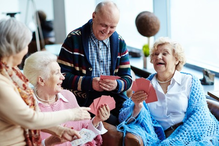 Gruppe von positiven Senioren Spielkarten Lizenzfreie Bilder