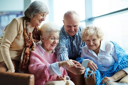 senior group: Group of senior friends watching photos on mobile phone Stock Photo
