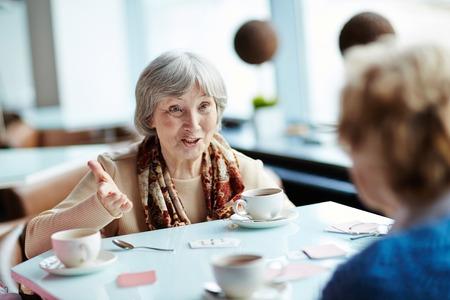 personas discutiendo: tarjetas juegan de la mujer mayor con su amigo Foto de archivo