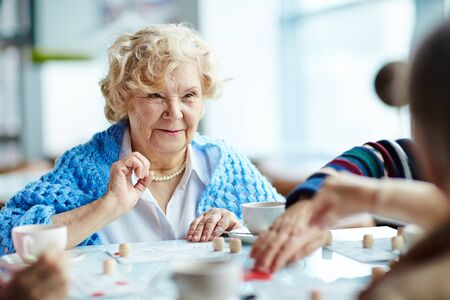 lotto: Senior woman playing lotto with friends Stock Photo
