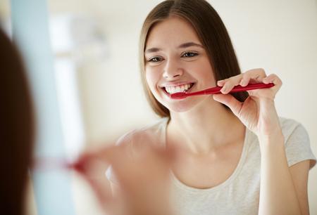 woman mirror: Yooung woman brushing her teeth at mirror