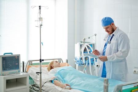 Doctor que se coloca en la cama con el paciente en cuidados intensivos