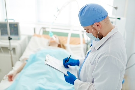 Hospital care: Doctor filling in medical card of a patient in icu