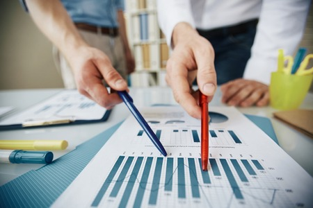 information point: Two office workers pointing at chart in business document during discussion