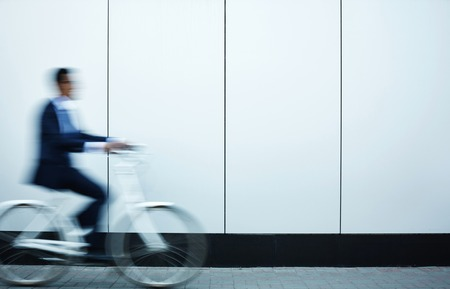 acceleration: Businessman on bicycle moving along wall of modern building Stock Photo